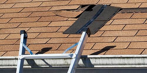 Damaged shingle roof with a patch in ready to be installed.